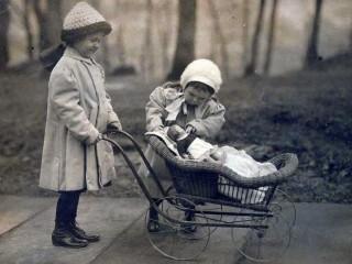 Bambini che giocano con carrozzeta e bambola