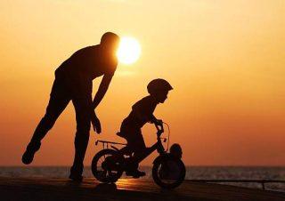 Padre che insegna al figlio ad andare in bicicletta