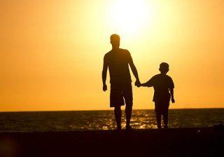 Padre che tiene figlio per mano