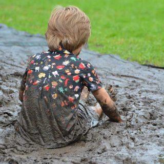 Bambino che gioca col fango